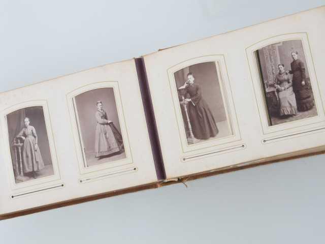 Album fra1880 årene. Brunt  skinn med presset ornamentikk på for og bakside, sort. Skinnet har opprinnelig vært rødbrun.  Metallspenne. To bilder på hver side.