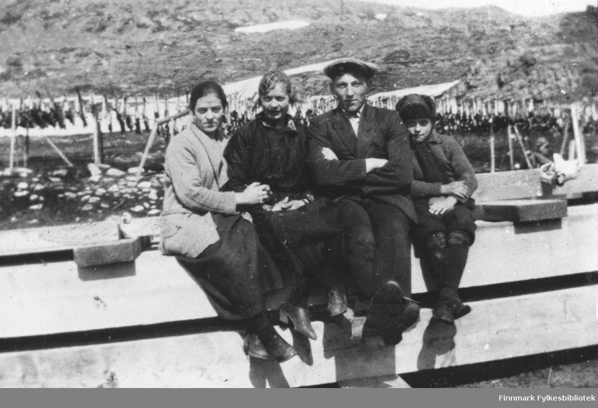 Arbeidsfolk sitter på en last med tømmer. Trygg Guldbrandsen er nr 3 fra v.  Resten er ukjente personer. Personene arbeidet på fiskebrukene  i Kongsfjord.  I bakgrunnen henger fisk på hjell Bildet er att om våren. Det ligger enda noen snøflekker rundt omkring.