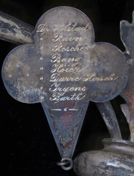 Kors av sølv, omgitt av en krans av eikeløv, montert på en pute trukket i sort fløyel.  Innrammet av forsølvet eføy. Kors, krans og ramme er nestet fast til puten. Korset er påført inngravert navn på den døde, mens anhenget under kransen har inngravert navn på giverne, Arendals leger.