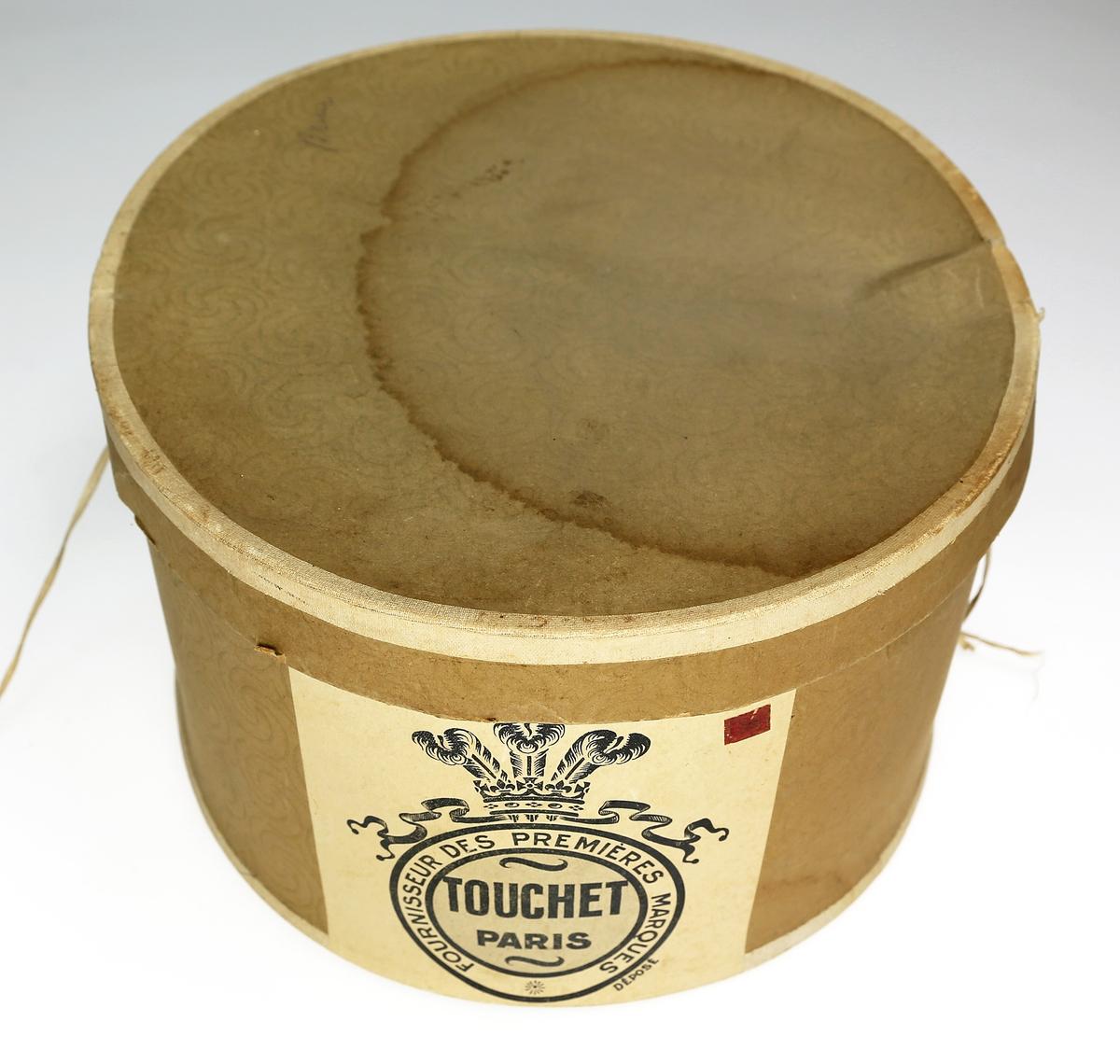 Flosshatt med bånd av ull, kanting med ripsbånd,  papir innvendig og skinnimitasjon rundt kanten.