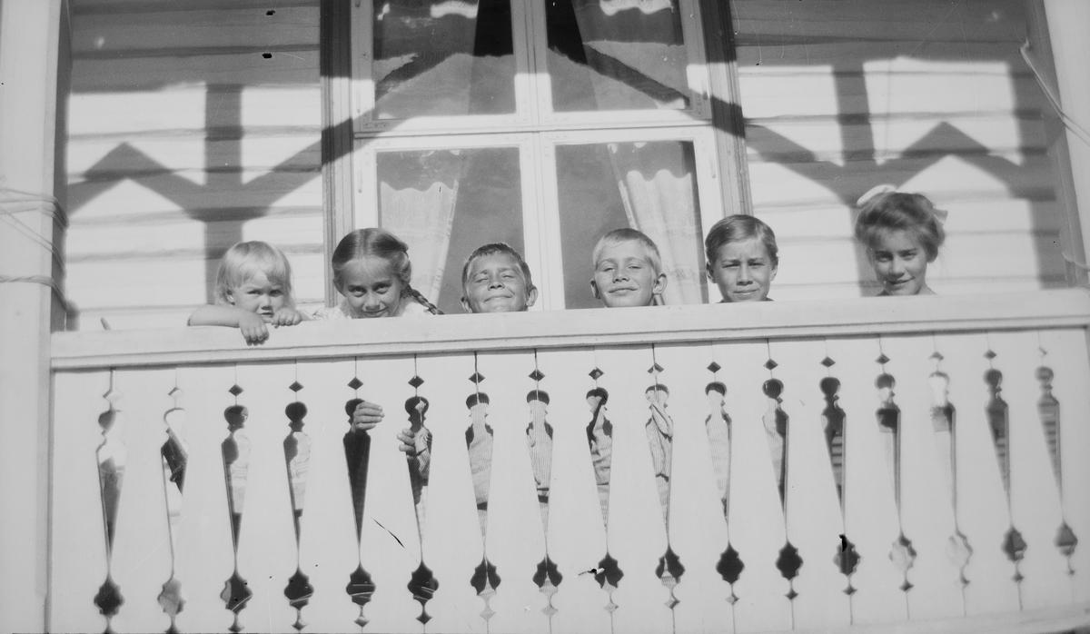 Fra venstre: Iacob, Ise (Louise), Christian Pierre, Erich Monsen, Haaken Christian og Celina Marie stikker hodene opp over et verandarekkverk.