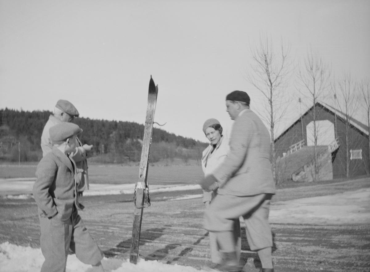 En siste skitur? Celina Marie, Christian Pierre, en mann og en gutt står rundt et par ski som er bundet sammen og satt ned i en siste rest av snø. De står på gårdsplassen på Linderud Gård.