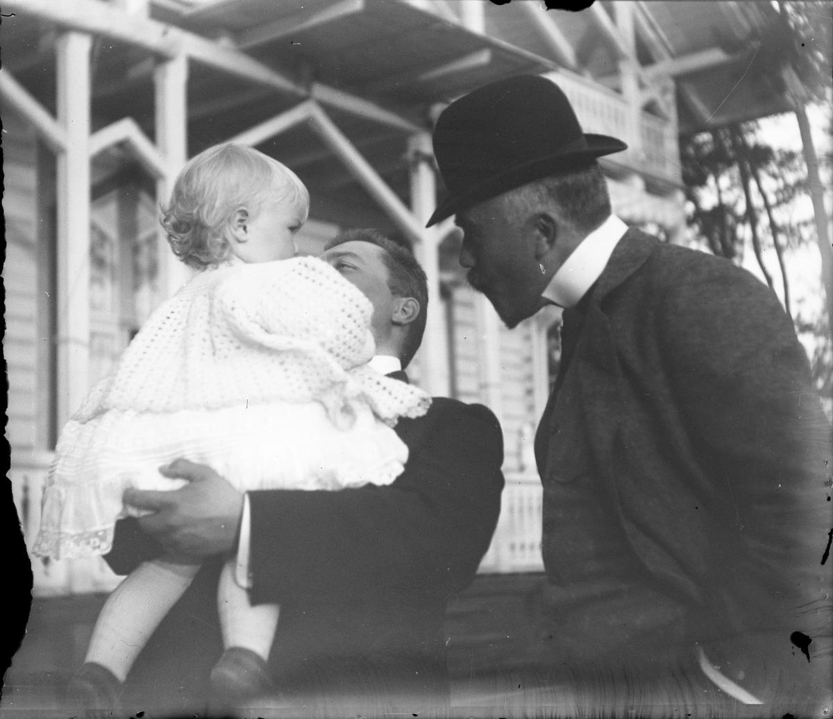 Arthur Knagenhjelm snakker med sin nevø Iakob, mens far Christian Pierre Mathiesen holder Iacob på armen.