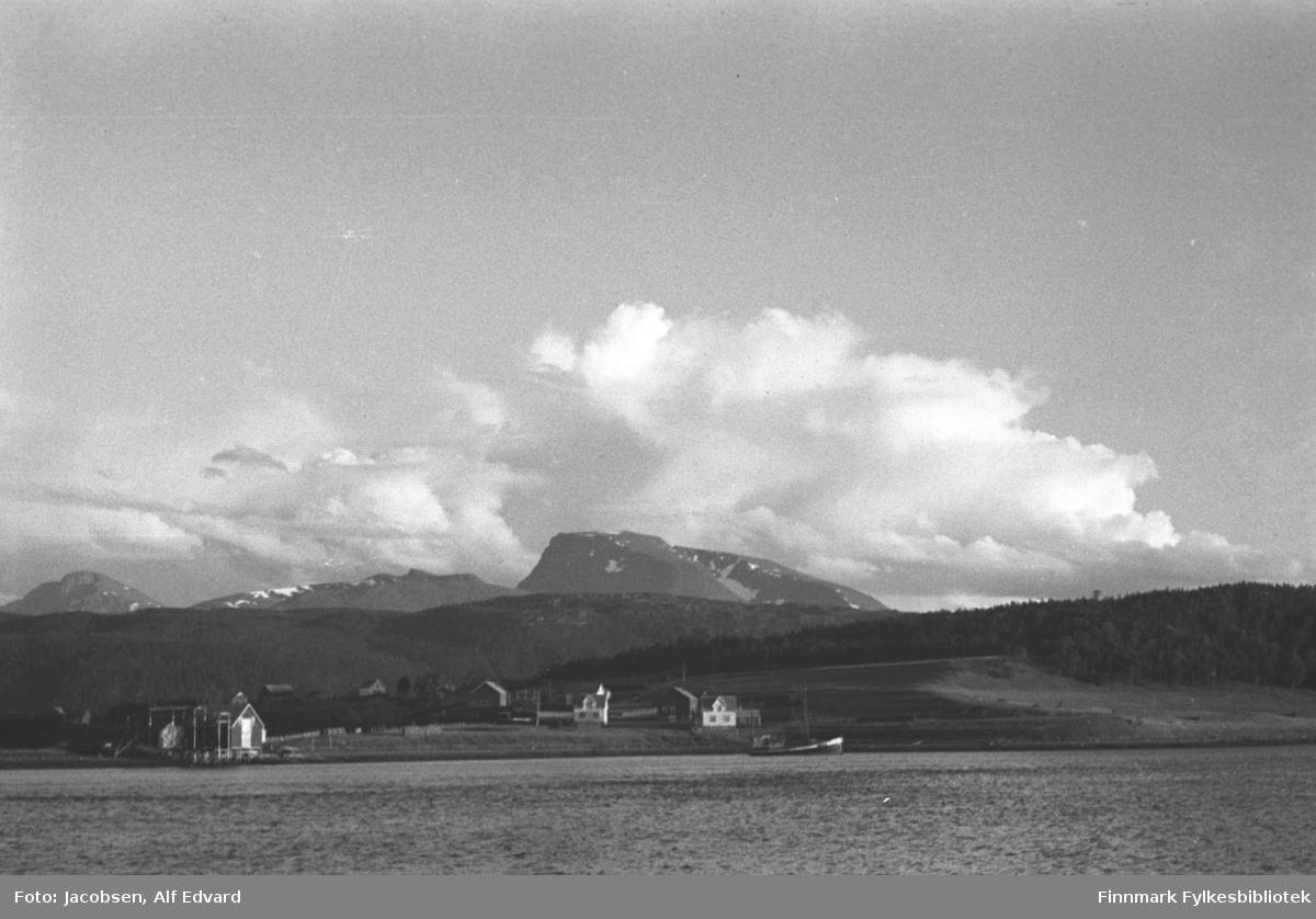 Et landskap tatt fra en båt. Det kan være en plass mellom Tromsø og Lødingen. Det er små bølger på sjøen som ligger nærmest kamera. En liten plass ligger i strandkanten. Det er noen hus, de fleste er hvite/lyse, og noen fjøs. Til venstre på bildet står en ganske stor bygning, deler av den er bygget på en kai. En fiskebåt ligger fortøyd nær land. Deler av terrenget fra husene og et stykke oppover ser ut som åkre eller annen pløyd mark. Lengre opp står en tett skog. Fjellene i bakgrunnen  ser ut til å ha lite vegetasjon. På de høyeste fjelltoppene ligger noen snøflekker. En stor sky-formasjon ses på himmelen over terrenget, ellers er himmelen klar og blå.