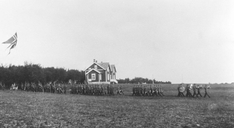 Vi antar at bildene er tatt i forbindelse med gjenopprettelse av Varanger batlajon 01.07.1934. Bildet viser marsjerende soldater ledet av militærkorps på eksersersplassen på Nybergmoen 1934. Soldaterhjemmet i bakgrunnen.