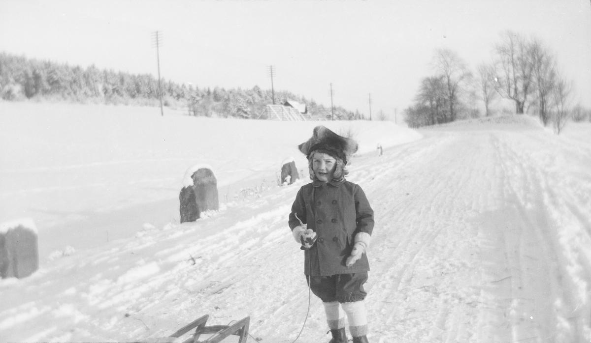 En gutt kledd i vinterklær, med en samisk stjernelue på hode, står med en kjelkesnor i hånden. Han står på en landevei med stabbesteiner. Veien er måkt/oppkjørt, men det er snø nok til å ake med kjelke. I bakgrunnen sees hus, strøm- og/eller telefonstolper og trær. Vi er sannsynligvis i område Linderud og Lunden, da bildet ble tatt Aker og i dag Oslo.
