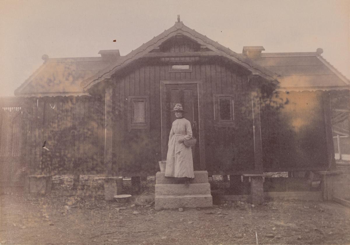 Julie (Hönsemor? - navnet ikke enda tydet) står foran et lite hus, som trolig er et hønsehus.