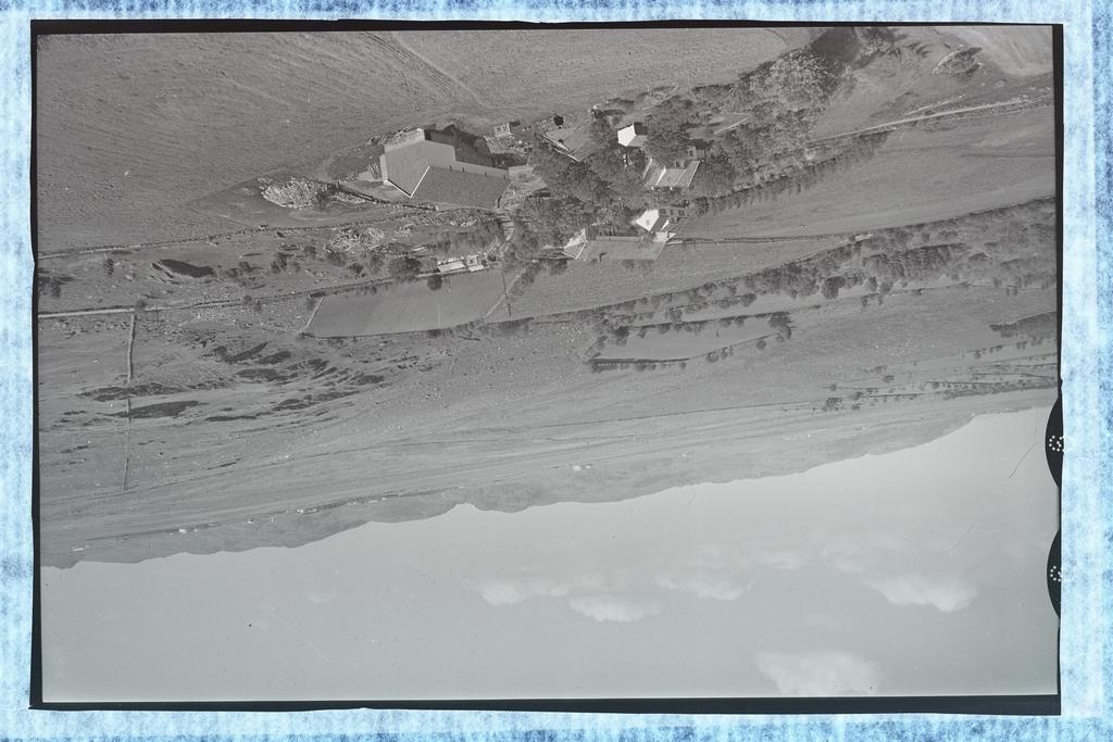"""Tjensvoll bruk 61/1, eigar Per Tjensvoll og Tjensvoll bruk 61/2, eigar Eivind Tjensvoll. I bakgrunnen Lende og Njåfjellet. Bruket som ligg for seg sjøl mot foten av Njåfjellet  må vera Mossige bruk 60/3, """"Botnen"""", eigar Ingolf Undheim. Undheimsvegen går på nordsida av husa og vert bort i skogen til venstre."""