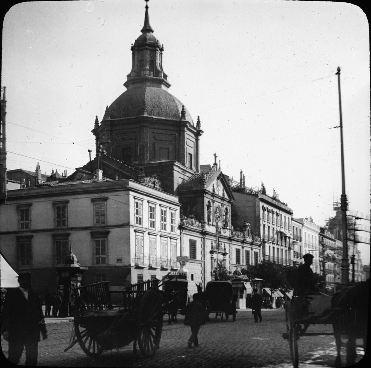 """Skioptikonbild med motiv av Iglesia de las Calatravas, Madrid (Spanien). Bilden har förvarats i kartong märkt: Höstresan 1910. Madrid 9. N:2. Text på bild: """"Calle de Alacadá""""."""