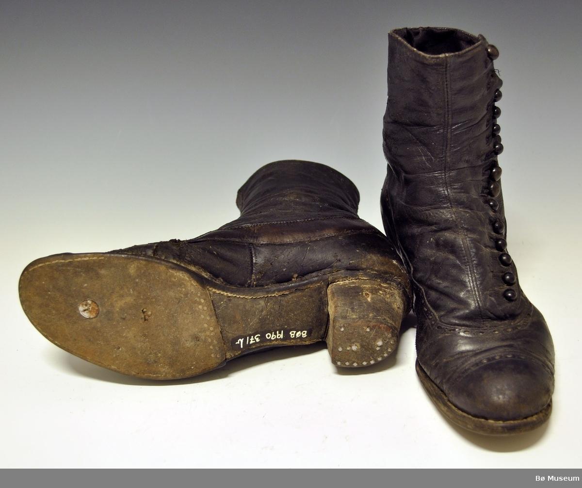 Lærstøvler med hel og lukning med knapper. Har vært brukt til folkedrakt/bunad. Knepping på skoens ytterside,, 12 stk knapper og knappehull. Dekor rundt tåhetten og langs sømmene med små hull.