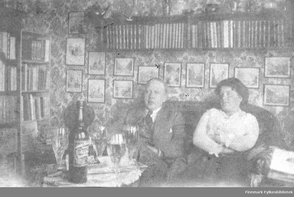 Skrivergaarden, kontoret 1915. Ukjent mann og dame fotografert i sofa. På bordet står det en flaske skotsk whiskey og 4 store glass. Muligens har man blandet en pjolter (alkoholholdig drikk av whiskey blandet med soda eller selters) i glassene. På veggen bak henger det mange fotografier og det er hyller med bøker. Veggen er tapetsert. Mannen er kledd i dress med slips og hvit skjorte, kvinnen har hvit bluse og muligens langt skjørt.