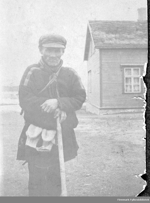 Skjolma-Per. Mann kledd i samisklignende kofte, med skyggelue, skjerf, belte med votter hengende i beltet, vandrestav, stokk eller stav i hendene. Man kan se et trehus i bakgrunnen, med gress/torv på taket. Et vindu er synlig.