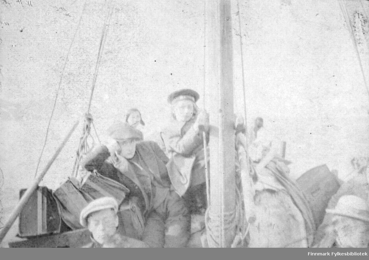 """""""Paa Tanafjorden 1917"""". Vi kan skimte 3 personer ombordi en seilskute. I front av bildet ser vi hodet på en mann med skyggelue/sixpence. Bak sitter det en gutt og lener hodet på ene hånden, han har sixpence og frakk, med dressjakke, genser og bukse under frakken. Ved masten står en gutt og holder seg fast, han har matroslue og en tykk frakkeliknende jakke. Helt bakerst skimter vi omrisset av et hode, muligens en kvinne. Til venstre i bildet ser vi også bagasje, mulighens kofferter. Nede i høyre hjørne kan man ane et hode med lys hatt og hattebånd."""