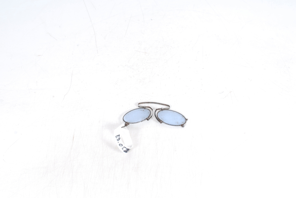 Form: Brilleglassene er ovale. De er festet til en fleksibel bøyle med neseklemme. Ved det ene brilleglasset sitter det en liten bøyle, eller hempe, til å feste en lenke i.