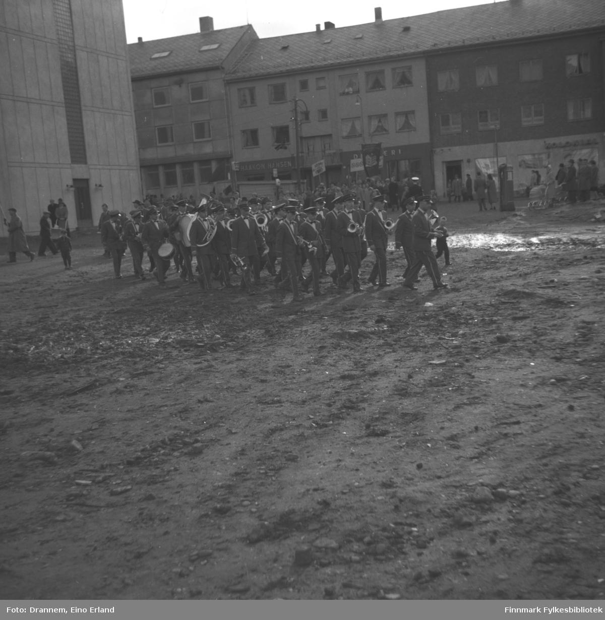 Et musikk-korps masjerer på Rådhusplassen i Hammerfest. Deler av rådhuset ses oppe til venstre på bildet.