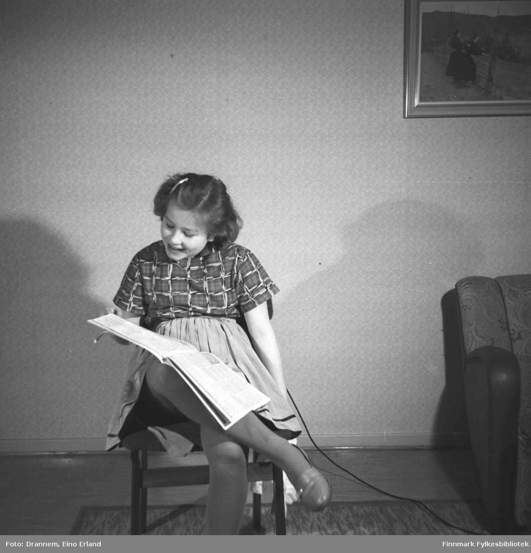 Turid Karikoski sitter og leser hjemme i familiens leilighet.