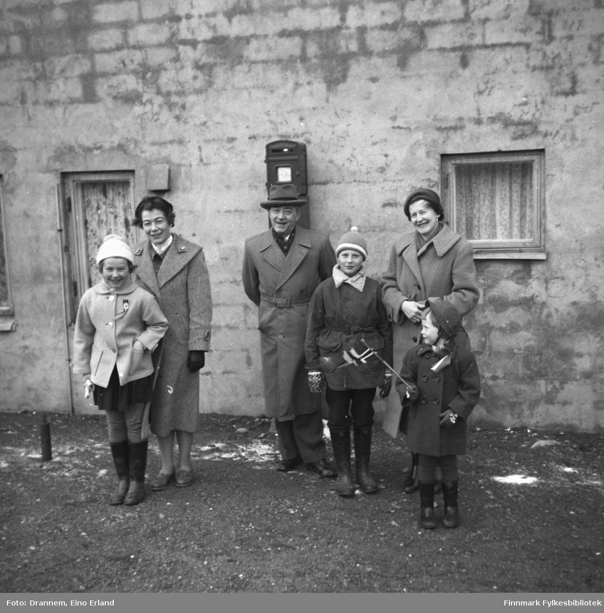 Tre voksne og tre barn klar for 17. mai-feiring utenfor en bolig i Hammerfest. Turid Karikoski står hel til venstre med moren Jenny Drannem like bak. De fire andre er familien Sørensen, fornavn ukjent.