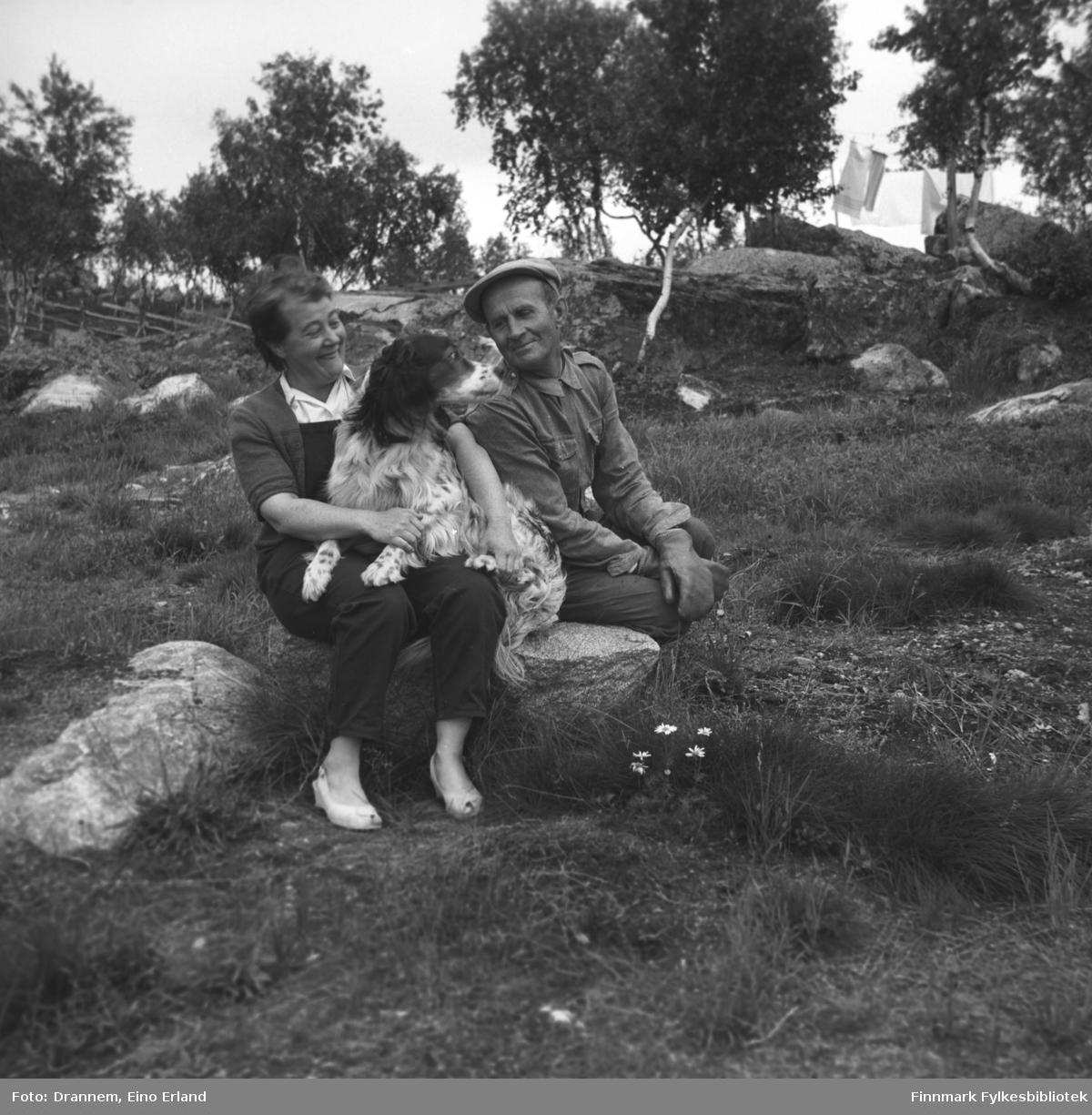 Sonja og Uuno Lappalainen sitter på en stein på gårdstunet med hunden Rexi på fanget.