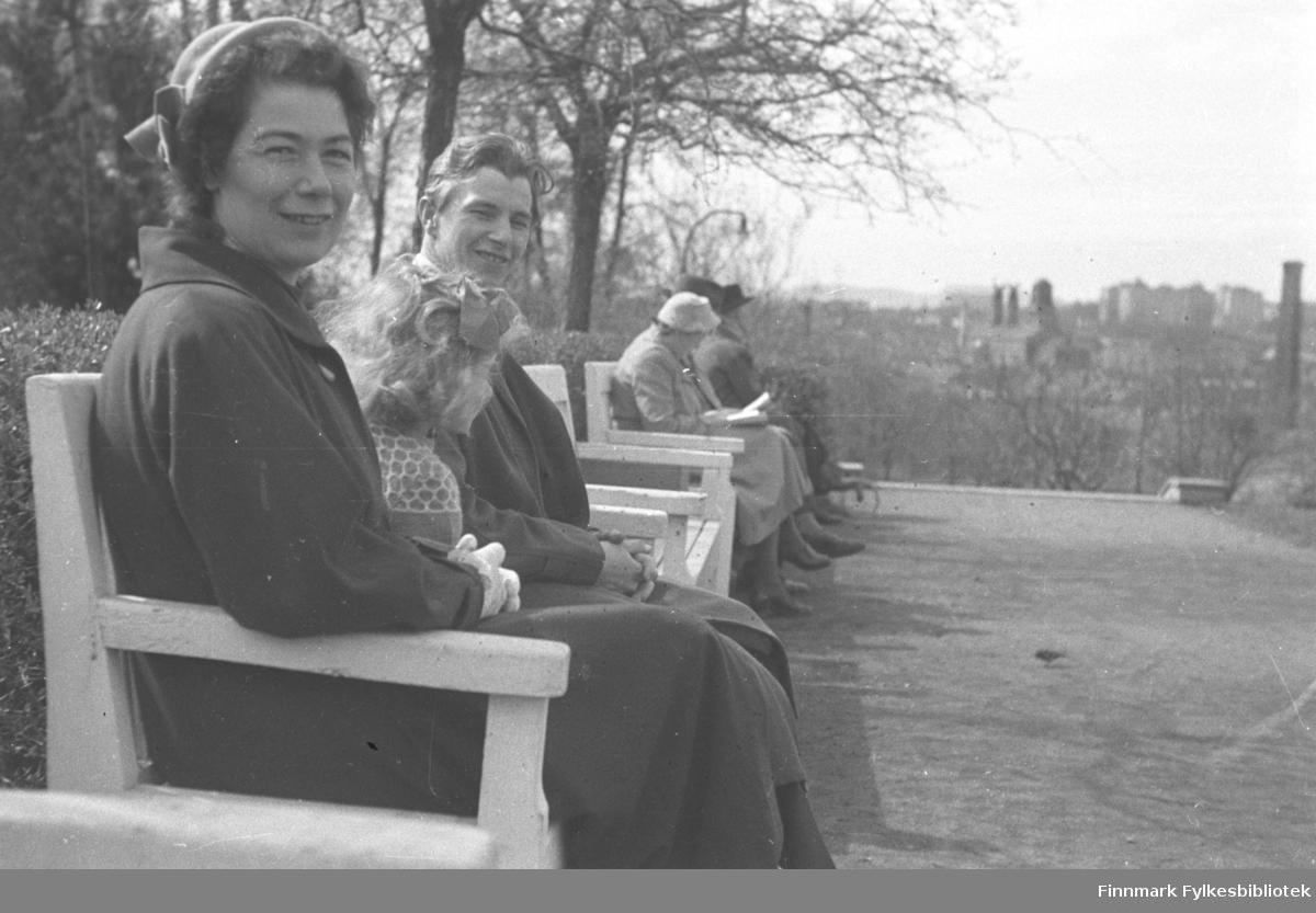 Familien Drannem sitter på en benk i en Park, Jenny nærmest kamera, Eino bakerst og Turid i midten. Bidet er tatt i Oslo.