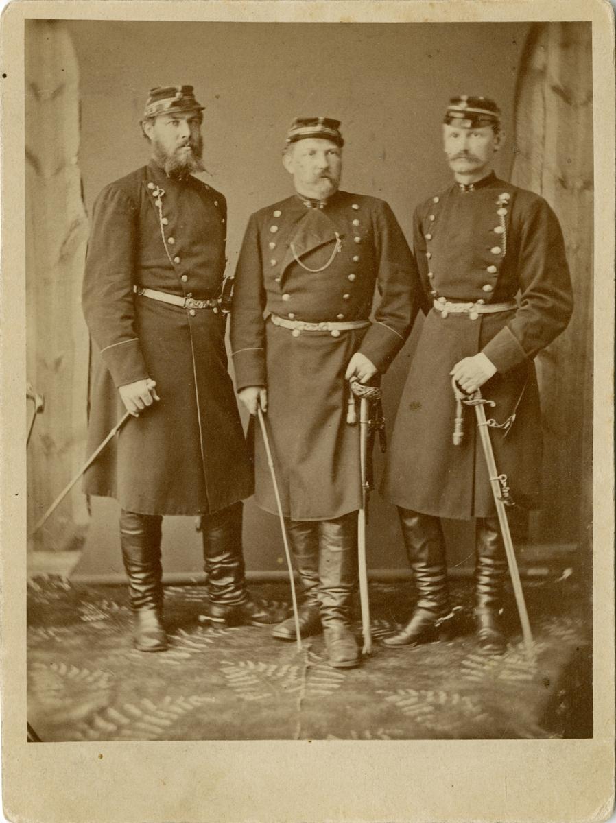 Porträtt av David Fabian Gustaf Adolf Ohlson (mitten), major vid Jönköpings regemente I 12. Omgiven av två okända officerare. Se även AMA.0008213, AMA.0008219, AMA.0008223 och AMA.0008228.  Gustaf Adolf Ohlson är känd som uppfinnare av olletröjan.