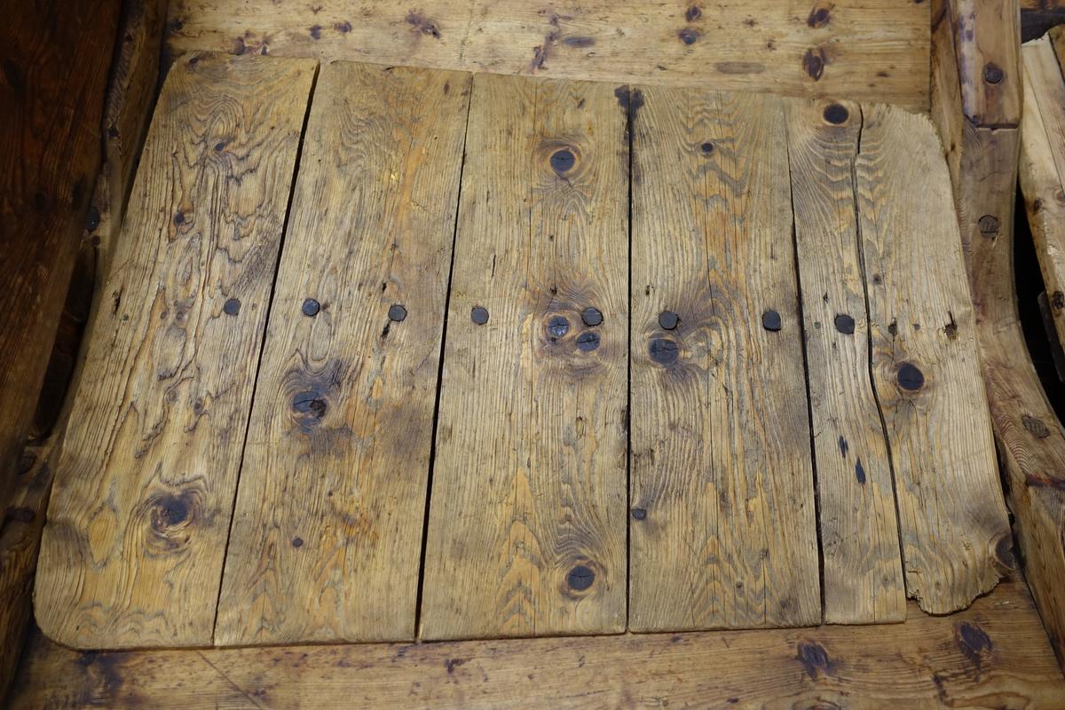 Et gulv til båten som består av fem bord spikret til en langsgående lekt, delene er også festet med trenagler