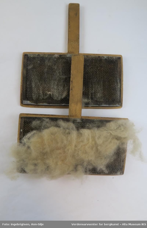 To rektangulære treplater med lærplater som er fylt med metallpigger. Dette blir brukt til å karde ull. I mellom platene er det fortsatt en stor dott med ull.