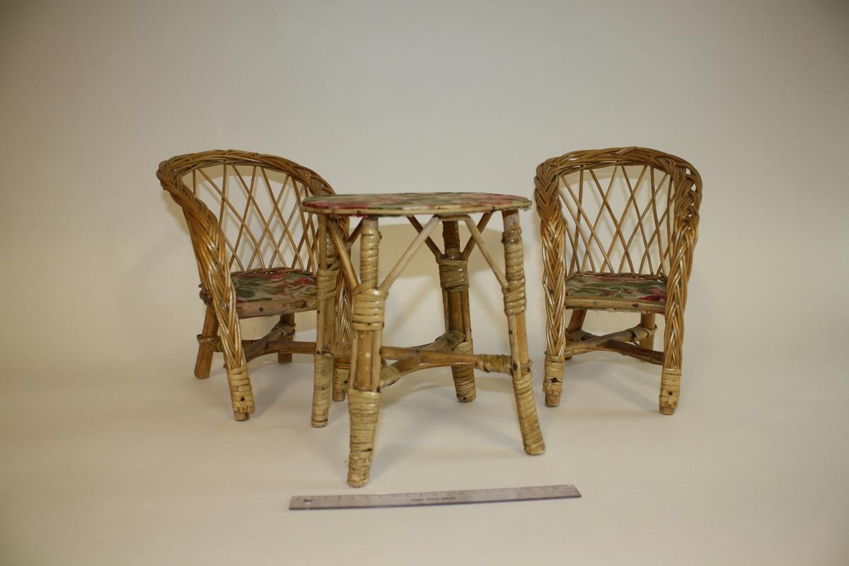 To stoler og et bord  Setet på de stolene, samt bordplaten har et trekk i blomstrete (rose) trekk.