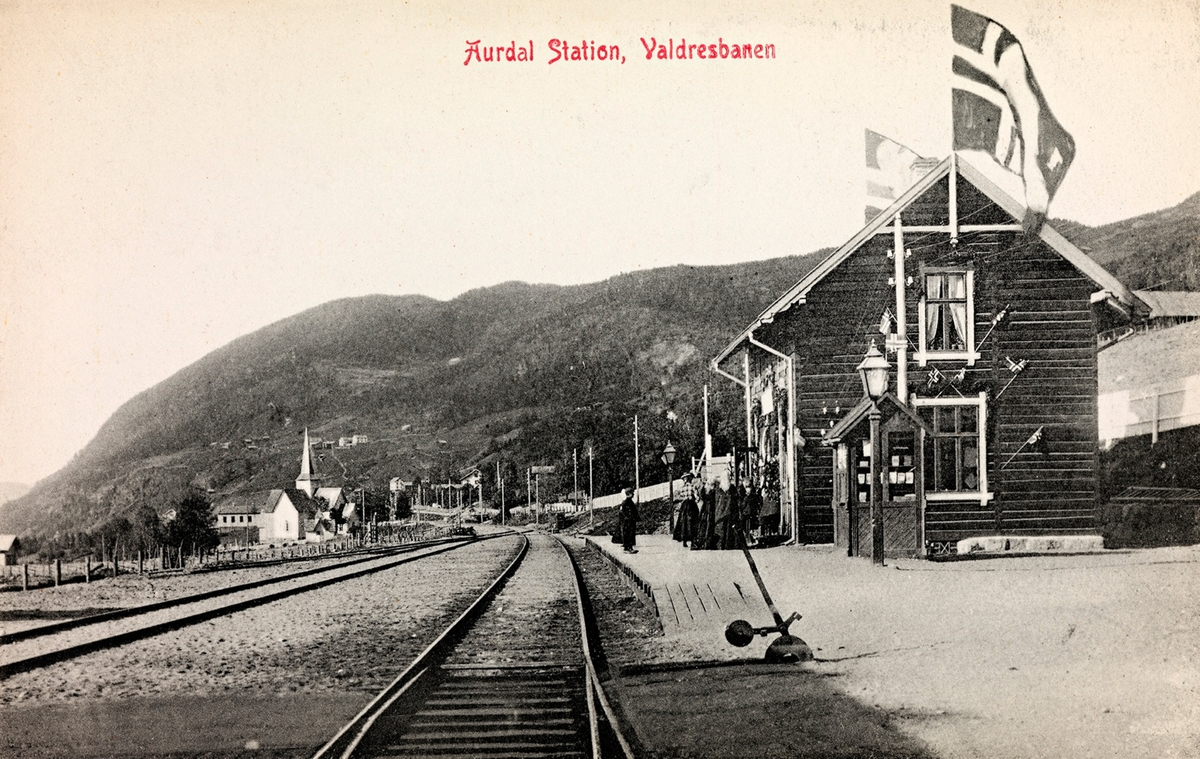 Aurdal jernbanestasjon, trolig fotografert i forbindelse med åpningen av Valdresbanen Dokka-Fagernes. Stasjonen er pyntet med flagg.