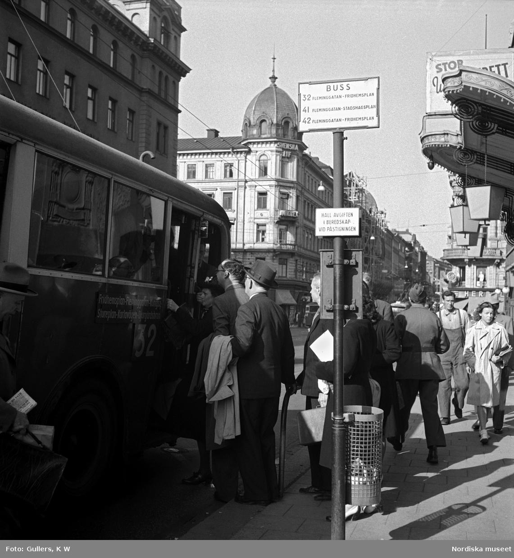 Passagerare köar till buss nummer 32 vid en hållplats utanför Oscarsteatern på Kungsgatan, Stockholm.