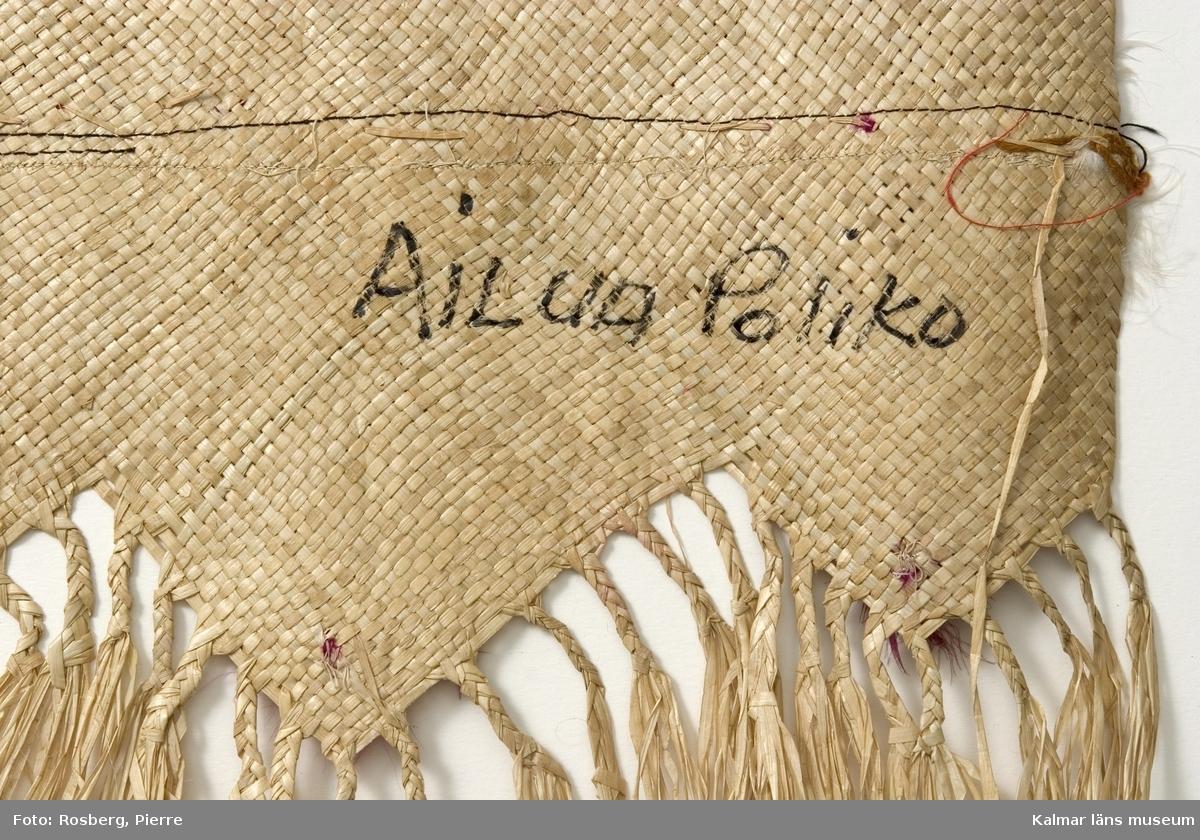 KLM 28465. Matta/kjol av pandanus (en palmväxt) och fjädrar. Plagget benämns 'ie toga. 'ie är en av tre sorters odlade palmväxter som används av samoanerna för mattorna. Mattan är mer att betrakta som ett ceremoniellt klädesplagg flätat av pandanus med fransar i båda ändarna och dekorerat med röda och några få vita fjädrar fastsydda med maskinsöm. Den här mattan, är ett ceremoniellt klädesplagg, den bärs runt midjan som en kjol, dubbelvikt så att man skall kunna se fransarna. Den hålls vanligen på plats av en gördel av barktyg. Följande namn finns påskrivna, på framsidan, KELEmet, TutuilA x Elsa, LUIT; på baksidan, AiLUA Poliko, LEALA SOLA. Därutöver ett nummer som tycks vara 10 finns också. Tutuila är för övrigt namnet på en sydöstsamoansk ö, vilken är huvudön i Amerikanska Samoa.