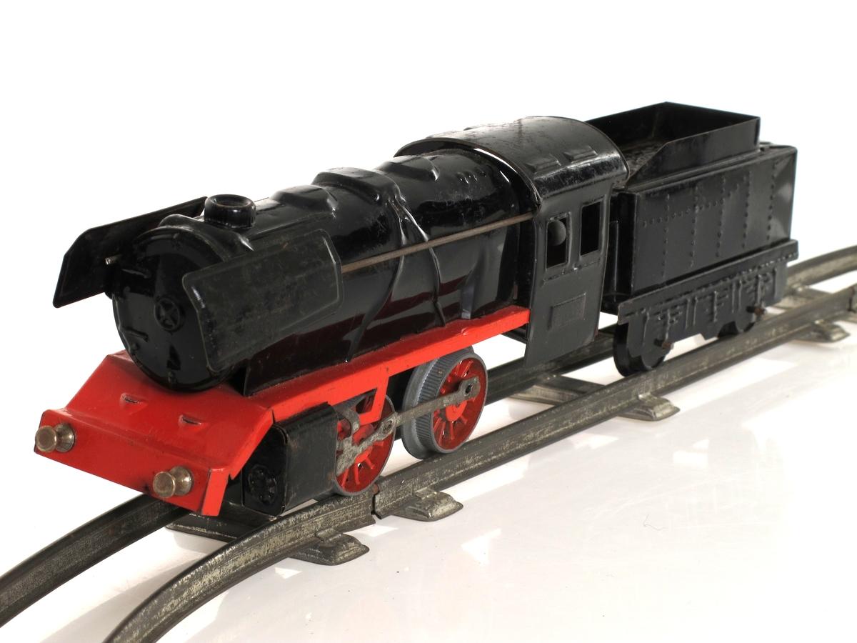 Togbane, med lokomotiv, tender, tre vogner og skinner. Lokomotivet har fjærmotor til opptrekk. Laget av tynne jernblikkplater, som er lakkert. Sort lokomotiv og tender, grønne vogner.   Deler: a. Lokomotiv b. Tender c.-e Vogner f-l   Skinner (6 stk buede, 1 stk rett)