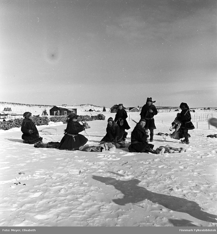Utenfor Kautokeino skoleinternat. Skolebarna banker dorkene i snøen. Fotografert påsketider 1940.