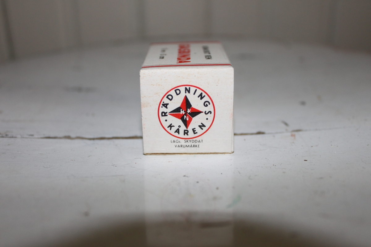 Gasbinda med förpackning i kartong. Tillhör Räddningskårens förbandslåda. På kanterna sitter Räddningskårens logga.  Kartong tillverkad av AB Kartonger & Tryck.