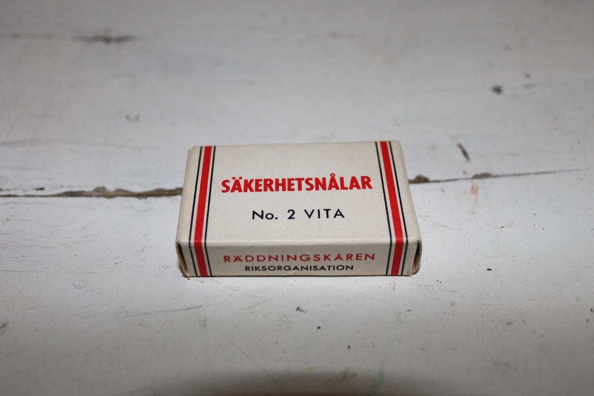 Säkerhetsnålar med förpackning i kartong. Tillhör Räddningskårens förbandslåda. För närvarande finnes sex säkerhetsnålar i förpackningen.