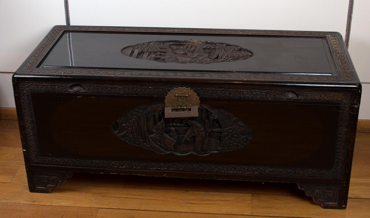 Kamferkiste med utskjæringer og firkantet hengelås.  Ovalt motiv på lokket samt de fire sidene er dekorert med blomstermotiv langs nedre kant.
