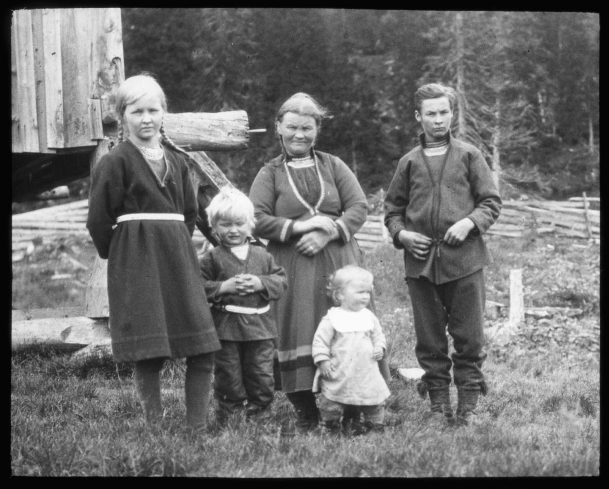 """N.569 a) """"Samer fra Tunnsjøen, Nord-Trøndelag. G.26. og R.58"""" står det på disse to glassplatene (to eks. av samme motiv). Gruppeportrett av en mor med sine 4 barn står oppstilt i gresset. Til venstre i bildet litt av en trevegg og bak gruppen stikker det frem store tømmerstokker. En skigard og granskog bakerst i bildet. Mor og de større barna har samekofter, barnet har kjole/forkle og smekke rundt halsen. Tunnsjøen (sørsamisk: Dåtnejaevrie) er den syvende største innsjøen i Norge, og ligger i Røyrvik og Lierne kommuner i Nord-Trøndelag fylke. Sjøen ligger 358 moh., er 222 m dyp på det dypeste og har et areal på 100 km². Samer fra Tunnsjøen er sør-samer."""
