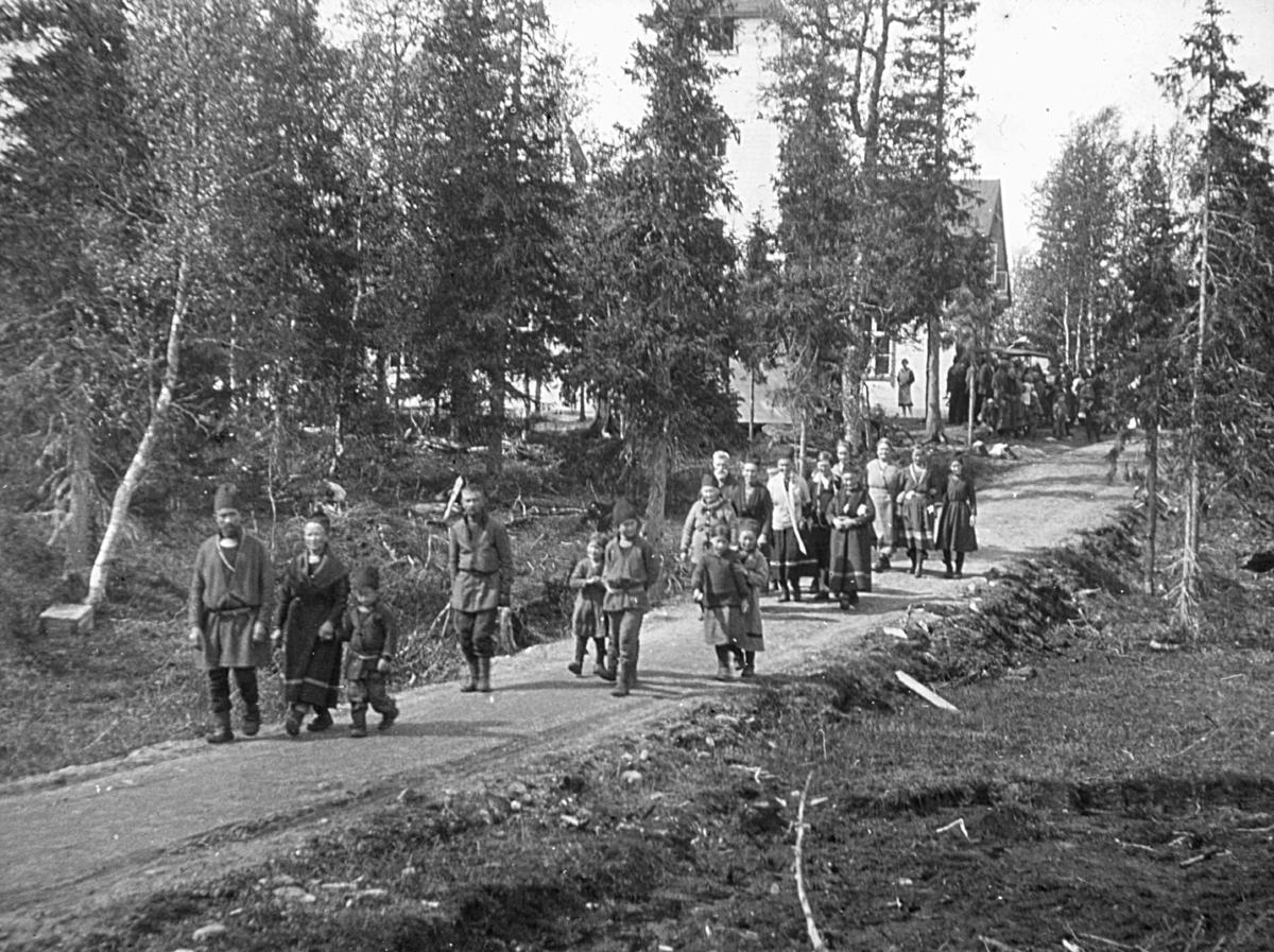 Gruppebilde av mennsker på vei fra kirke. Samiske kofter.
