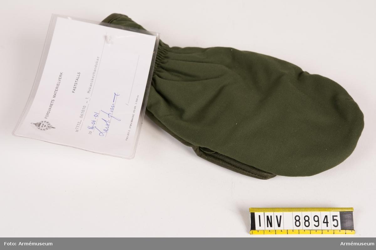 """Mekanikerhandske för höger hand med öppning för tummen och fingrarna. Invändigt faststydd etikett med tvättråd, materialbeskrivning och tre kronor samt årtalet 1984 och tillverkare SM of Sweden. Vidhängande modellapp med text: """"Försvarets materielverk. Fastställs. M 7332-061010-1. Mekanikerhandskar 1986-06-01 (oläslig underskrift)."""""""