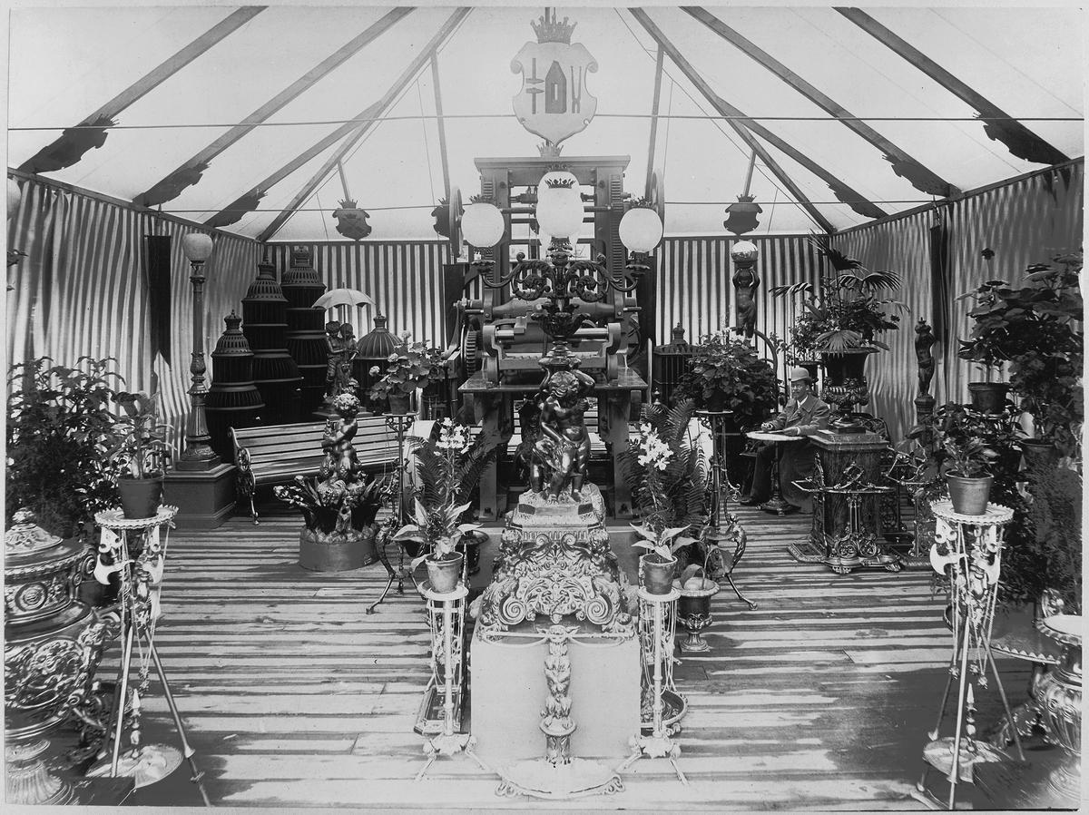 Blomsterarrangemang i monter om Bolinders gjutjärnsprodukter på utställning i Göteborg 1891.