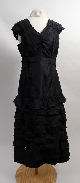 Klänning, svart sidentaft. Urringad, ärmlös. 8 volanger på kjolen. Skärp. Söndrig i sömmar. Blixtlås i sidan. Kort jacka i sammet, tillhörande samma klänning.