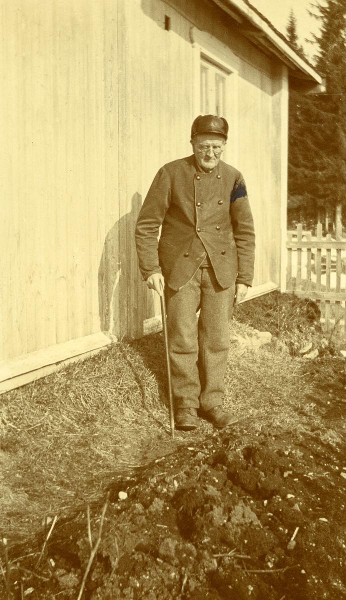 Gammel mann med briller og stav. Stående ved husvegg. Paul Gregersen, søndre Sørlie, Langtjernåsen (28/12 1847 - 15/11 1928) (78 år gammel)