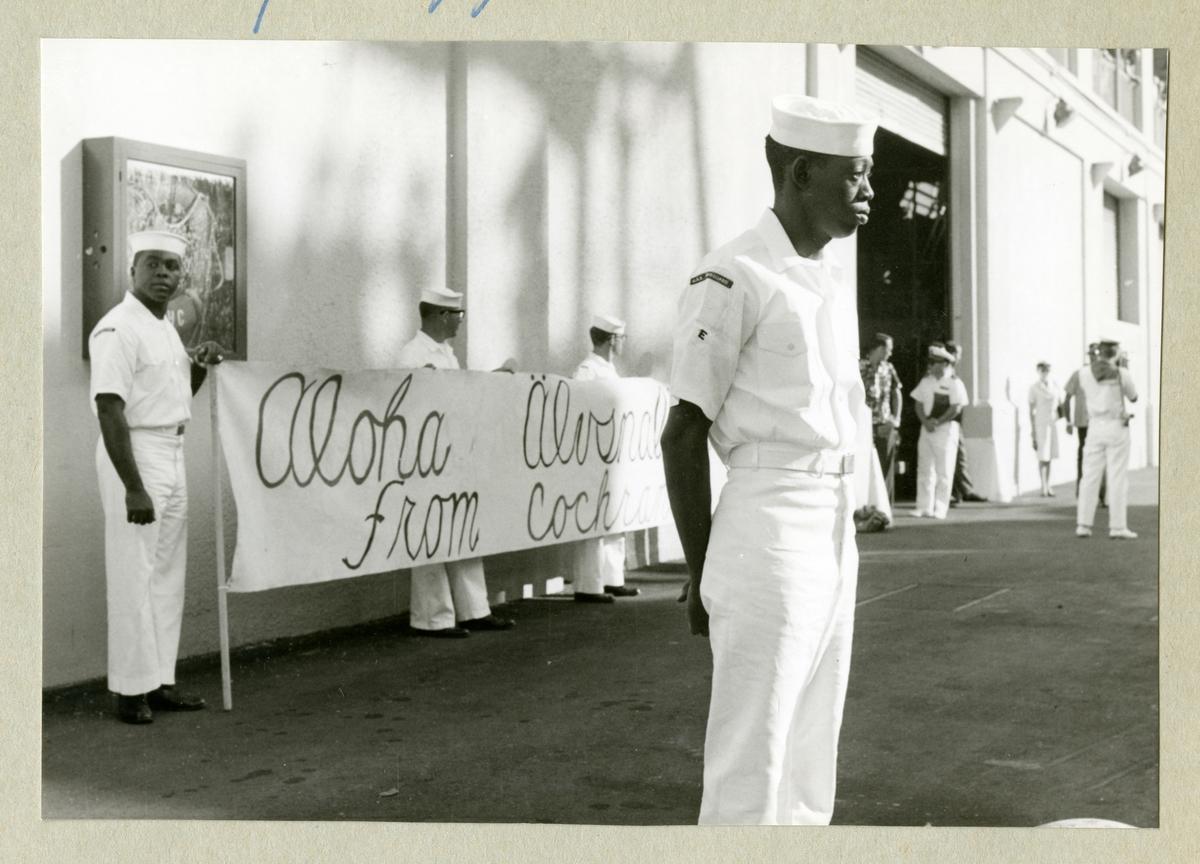 Bilden föreställer män i vita uniformer som står tillsammans med en välkomstskylt med text på. Bilden är tagen under minfartyget Älvsnabbens långresa 1966-1967.