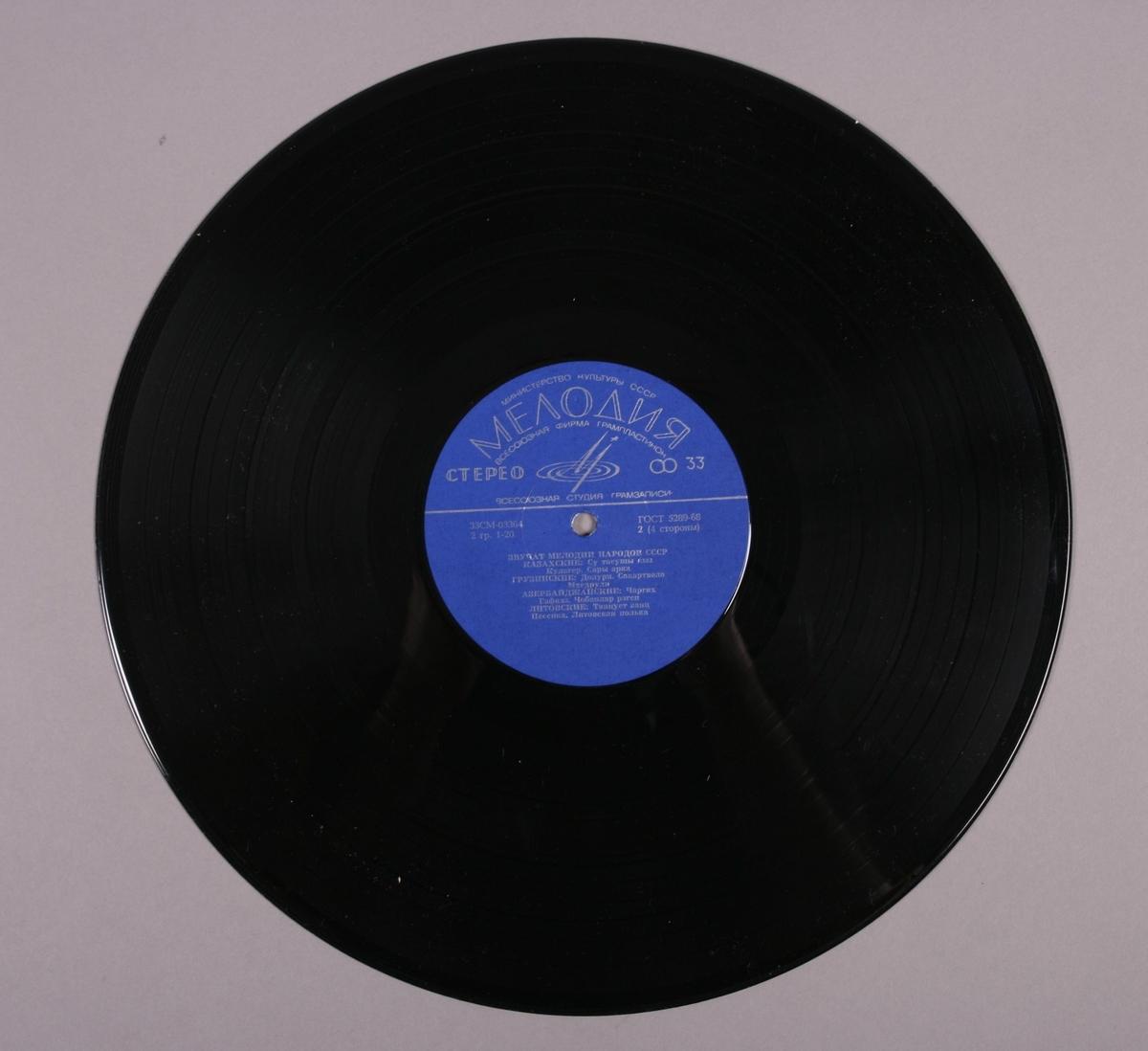 """Grammofonplate i svart vinyl og uoriginalt plateomslag i papir. Påskrift på baksiden av plateomslaget hvor det står """"Ulike meloder fra forskj. områder!"""".  Plata ligger i en plastlomme."""