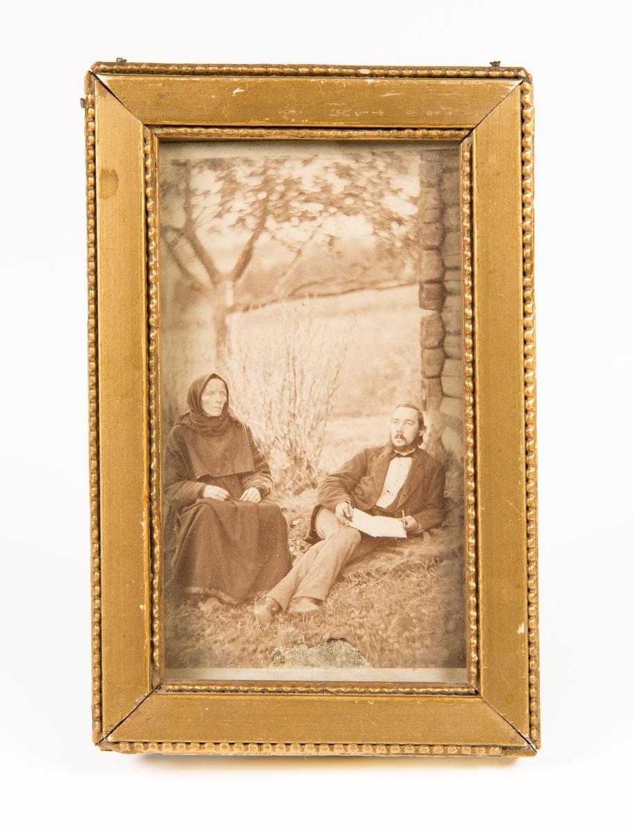 Ung mann og gammel kone. Utendørs. Laftet hushjørne og et tre ses i bakgrunnen.