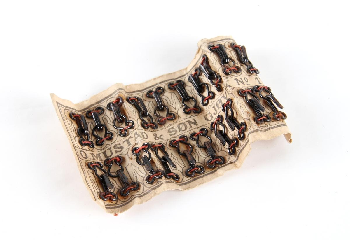 Et brett med 20 ubrukte hekter festet på original emballasje med tråd.