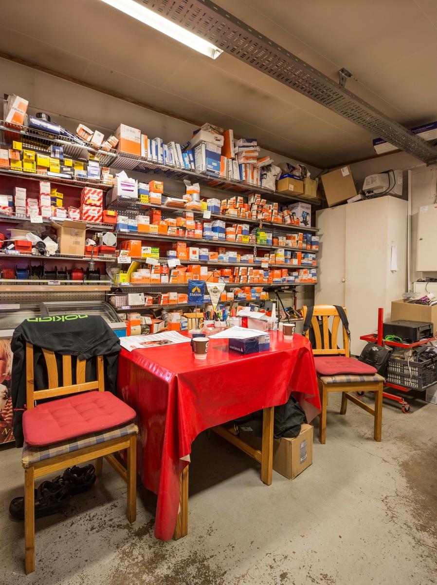 Statoil Hemnes. Hvilerom interiør bak butikken med spisebord og stoler. Lagerhyller med oljefiltre.