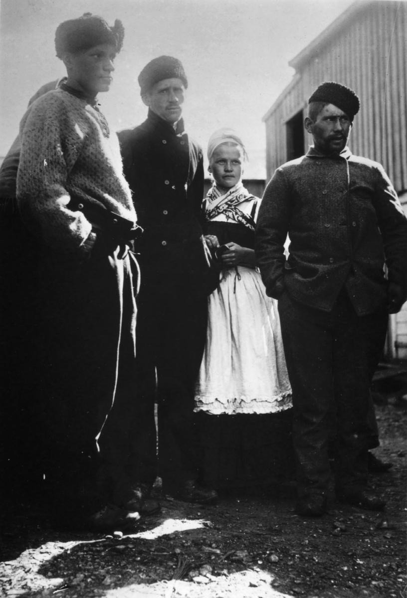 Russiske fiskere i Kiberg 1899. På bildet står en nordmann til venstre og to russiske menn med ei russisk jente. De lytter til et omreisende musikkselskap, skriver Ellisif Wessel på baksiden av originalbildet.