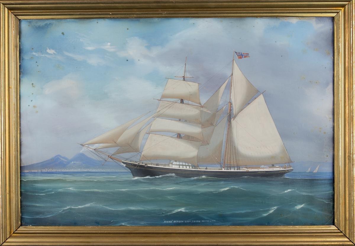 Skipsportrett av skonnertbrigg ANNA med full seilføring utenfor Napoli med vulkanen Vesuv i bakgrunnen. Skipet fører norsk handelsflagg med svensk-norsk unionsmerke. Ser flere av mannskapet på dekk.