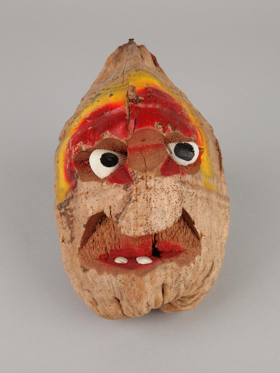 Mannshodefigur, laget av en nøttefrukt. Utskåret for øyne og munn. Øynene er hvite skjell, påmalt sorte flekker. Tenner av hvite skjell.