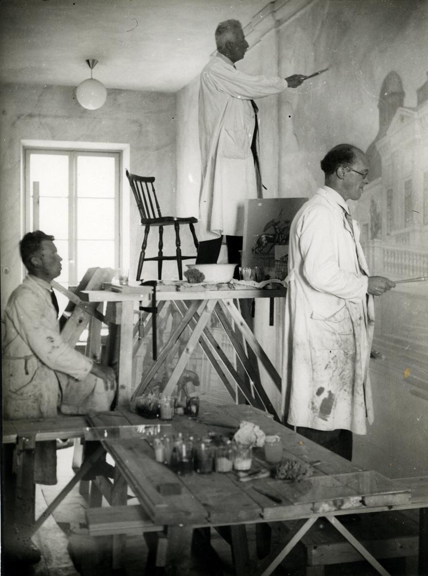 Prins Eugen med medhjälpare målar väggmålningen i Stagneliusskolans trapphus.